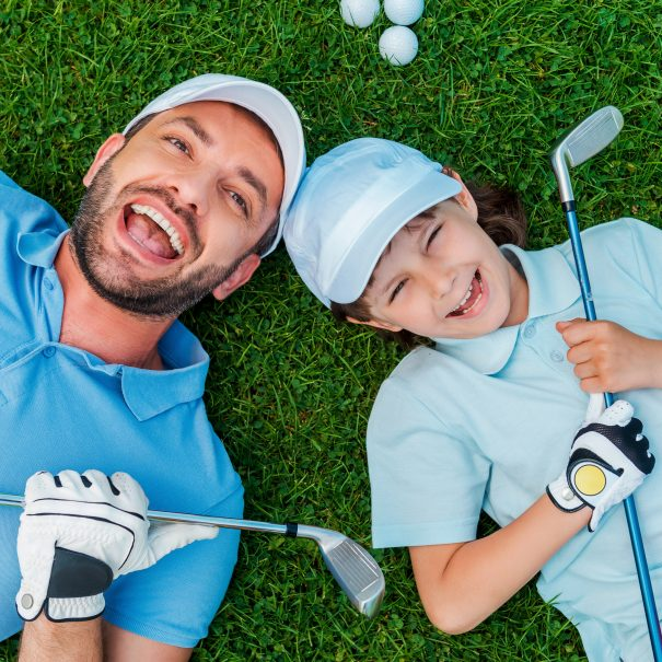 Top view of cheerful little boy and his father holding golf clubs and smiling while lying on the green grass